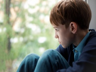 Sad teen sitting on window